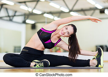 smiling teenage girl stretching on mat in the gym - fitness,...