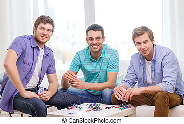 happy three male friends playing poker at home - leisure,...