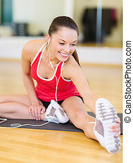 smiling girl with smartphone and earphones in gym - fitness,...