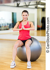 young woman doing exercise on fitness ball