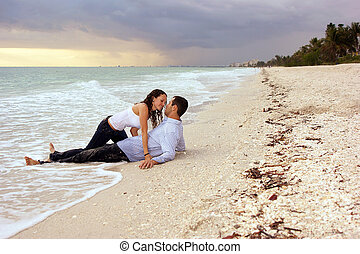 fantasy woman about to kiss man on beach at sunset - man is...