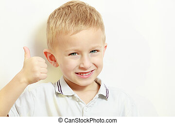 Happy childhood. Smiling blond boy child kid showing thumb...