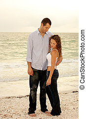 young man holding woman in front of ocean looking down at...