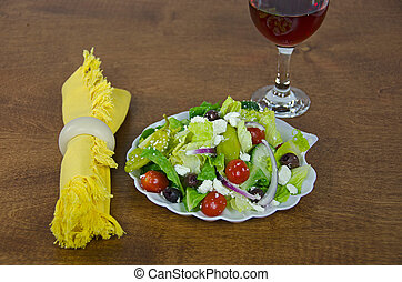 Greek salad and wine - Greek salad with red wine on wooden...