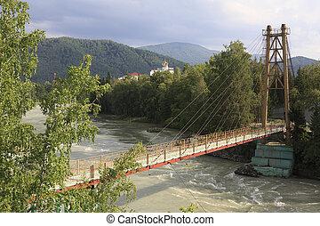 Suspension bridge on the mountain river Katun. Sanatorium Crown Altai.