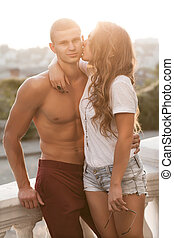 Young beautiful couple in love on sunset. Soft sunny colors.
