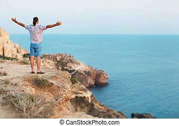 Man standing on a rock by the sea Concept of freedom