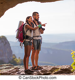 Two backpackers in mountains. Young couple examining the...
