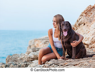 Portrait of a woman with her beautiful dog sitting outdoors.
