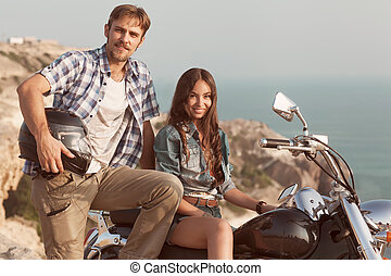 Stylish couple on a motorcycle. He put his foot on the...