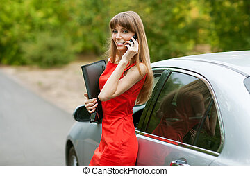 Elegant business lady in a red dress standing in front of her car. She is holding a black folder with documents and talking on the phone.