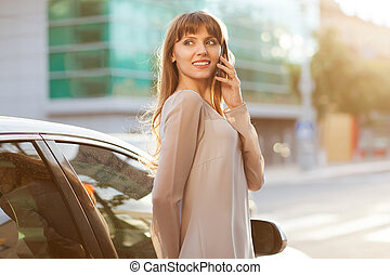 Pretty young business woman using mobile phone outdoor She...