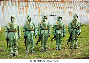 A group of soldiers with guns in their masks and protective...