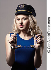 Beautiful girl with handcuffs and a police cap Isolated on...