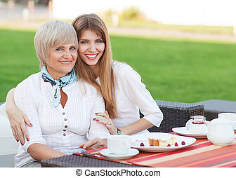 adult mother and daughter drinking tea or coffee