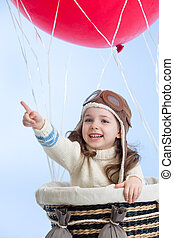 kid girl playing on hot air balloon on the sky background