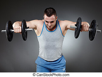Training with dumbbells - Fit young man training with...