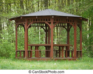 Brown wooden arbour at edge of forrest - Small brown wooden...