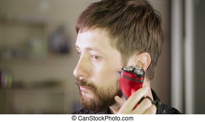 Shaving beards - Young man shaves his beard electric razor