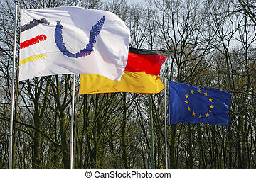 two european union and one german flag stream in the wind