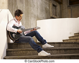 young guitar player - young man sitting on steps playing...