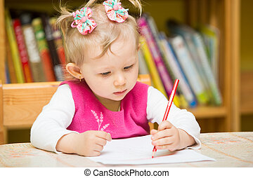 Cute child girl drawing with colorful pencils in preschool...
