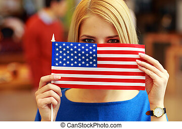 Portrait of a student peeking behind flag of USA