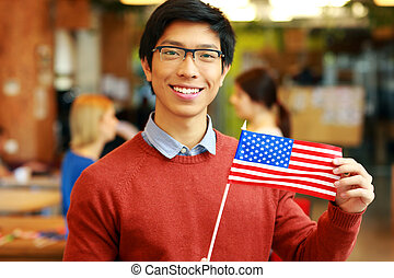 Smiling asian student holding flag of USA