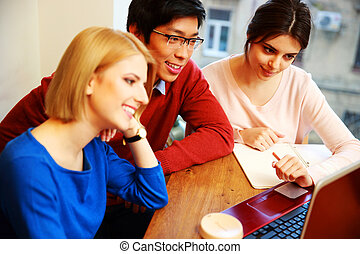 Happy students working on laptop together