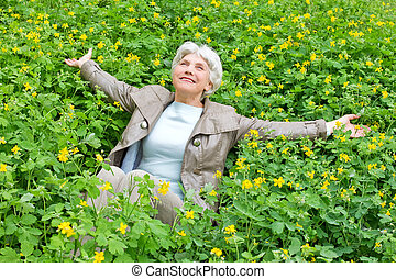 beautiful elderly woman on a glade - Happy beautiful elderly...