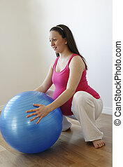 Young smiling pregnant woman doing squatting exercise with fitness ball.