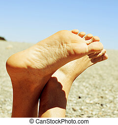 relaxing at the beach - closeup of bare feet of a man...