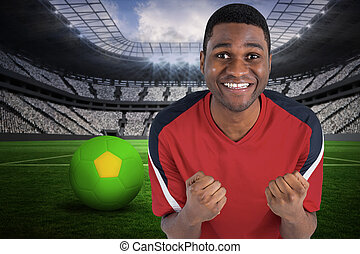Composite image of excited handsome football fan cheering -...