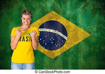 Excited football fan in brasil tshirt against brazil flag in...