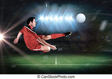 Football player in red kicking in a football pitch under...