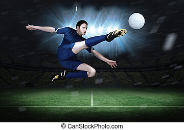 Football player in blue kicking in a football pitch under...