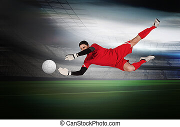 Fit goal keeper jumping up in a large football stadium with...