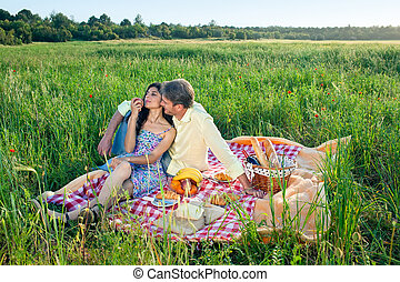 Romantic couple enjoying a summer picnic sitting on a red...