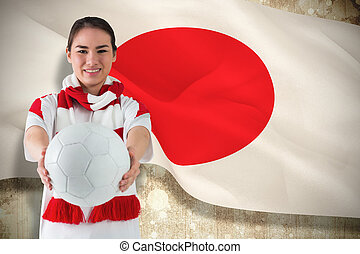 Composite image of football fan in white wearing scarf holding ball against japan flag