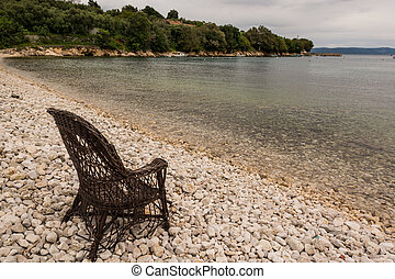 Chair on a beach covered with pebbles - Chair on a beach...