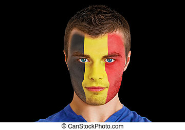 Composite image of serious young beligan fan with facepaint...