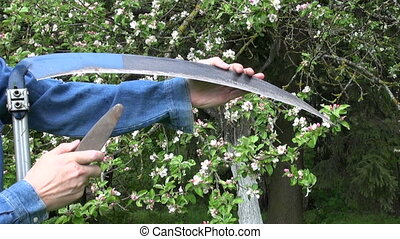 sharpening scythe tool with stone in spring farm garden