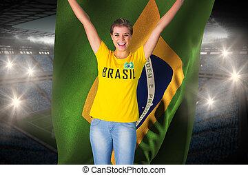 Excited football fan in brasil tshirt holding brasil flag...