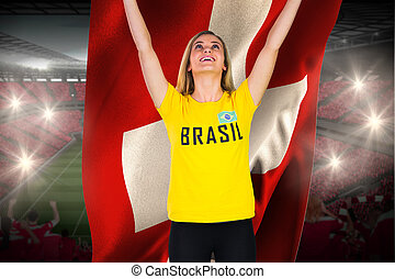 Excited football fan in brasil tshirt holding swiss flag against vast football stadium with fans in red