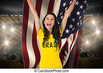Excited football fan in brasil tshirt holding usa flag...