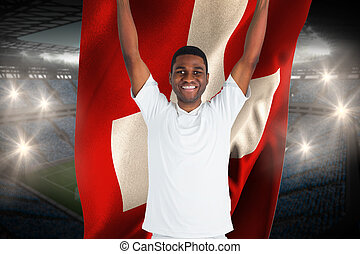 Excited handsome football fan cheering holding swiss flag against large football stadium with fans in blue