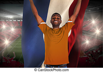 Cheering football fan in orange jersey holding netherlands...