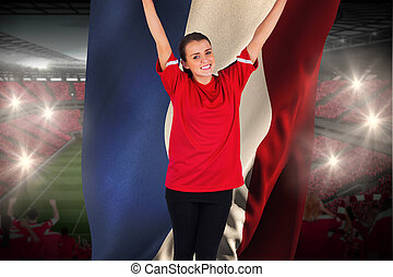 Excited football fan in red cheering holding france flag...