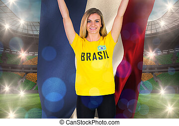 Excited football fan in brasil tshirt holding netherlands...