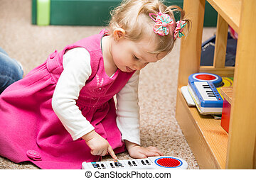 Little child girl playing in kindergarten in Montessori...